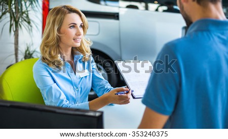 Photo of young female consultant and buyer. Young man buying new car in car showroom. Signing of contract and insurance - stock photo