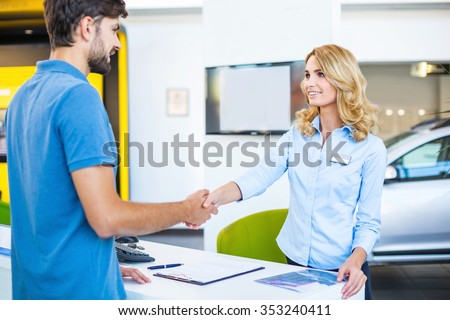 Photo of young female consultant and buyer. Young man buying new car in car showroom. Signing of contract and insurance. Man and woman shaking hands - stock photo