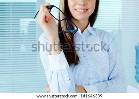 Photo of young female holding eyeglasses - stock photo