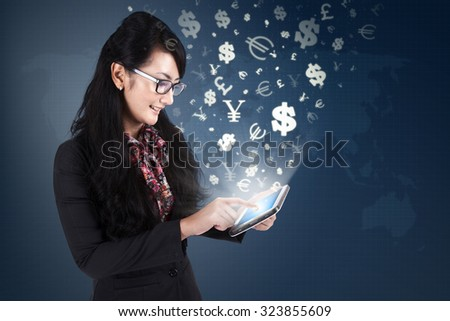 Photo of young female worker using digital tablet with currency symbols flying away. Making money online concept
