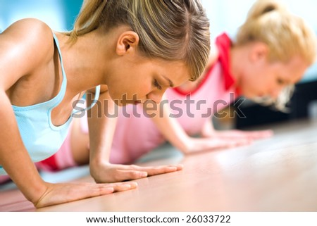 Photo of young girl doing difficult exercise for arm biceps on the floor