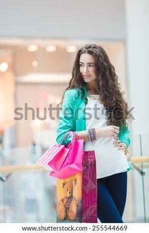 Photo of young joyful girls with shopping bags on the background of shop windows. Attractive smiling blonde on shopping in mall. Young woman shopping - stock photo