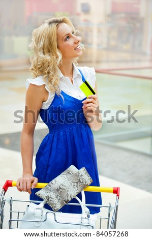 Photo of young joyful woman with shopping bags inside mall driving her trolley full of clothes, bags, shoes and other purchases - stock photo