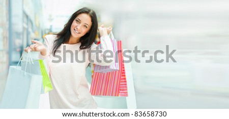 Photo of young joyful woman with shopping bags on the background of shop windows at mall. She is smiling and walking. Lots of Copyspace - stock photo