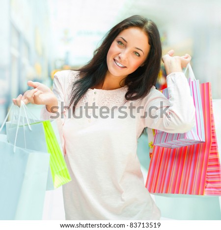 Photo of young joyful woman with shopping bags on the background of shop windows at mall. She is smiling and walking
