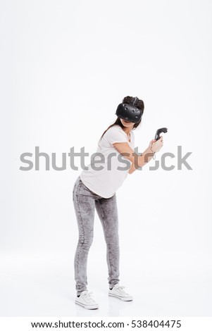 Photo of young lady wearing virtual reality device while holding joysticks over white background.