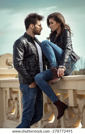 Photo of young loving couple looking at each other outdoor - stock photo