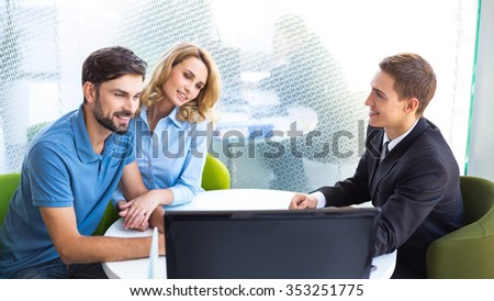 Photo of young male consultant and couple. Young woman and man choosing and buying new car in auto show. Concept for car rental - stock photo