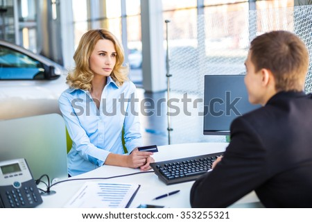 Photo of young male consultant and female buyer. Young woman buying new car in auto show. Buyer holding credit card. Concept for car rental - stock photo