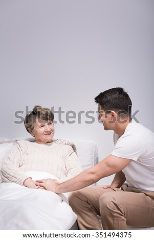Photo of young man helping his ill grandmother