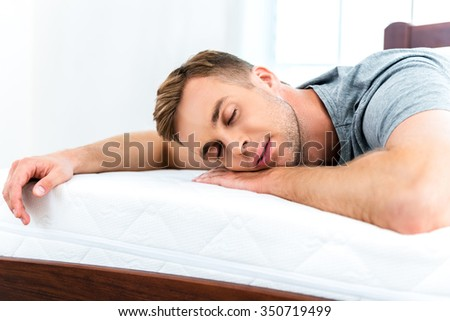 Photo of young man sleeping on nice white bed. Young man demonstrating quality of mattress - stock photo