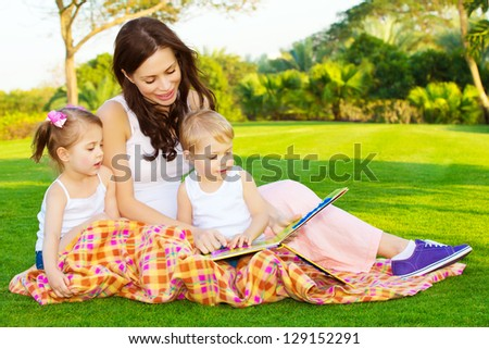 Photo of young mother with two cute kids reading book outdoors in spring time, happy mom teaching her children in the park, day care, beautiful woman with son and daughter having fun on backyard - stock photo