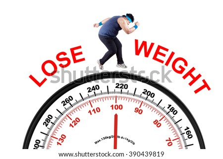 Photo of young overweight person with lose weight text, running above scale. Isolated on white background - stock photo