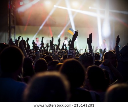 Photo of young peofans applauding to famous music band, nightlife, DJ on the stage in the club, crowd dancing on dance-floor, night performanceple having fun at rock concert,  - stock photo