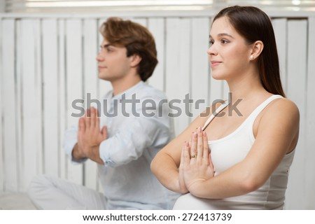 Photo of young pregnant woman practicing yoga with her husband. They meditating in lotus position with folded hands - stock photo