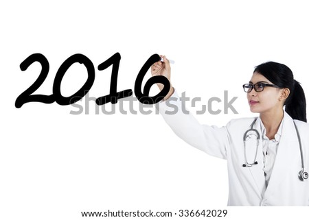 Photo of young pretty doctor with uniform, writes numbers 2016 on the whiteboard, isolated on white background
