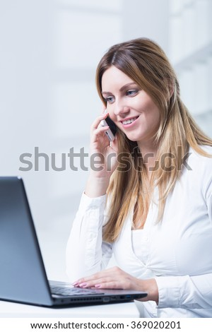 Photo of young saleswoman with headset and laptop - stock photo