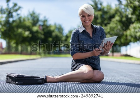photo of young smiling business woman sitting on a metal floor with tablet pc - stock photo
