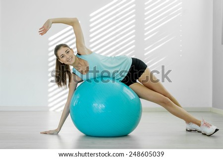 Photo of young smiling woman doing workout with a gym ball - stock photo