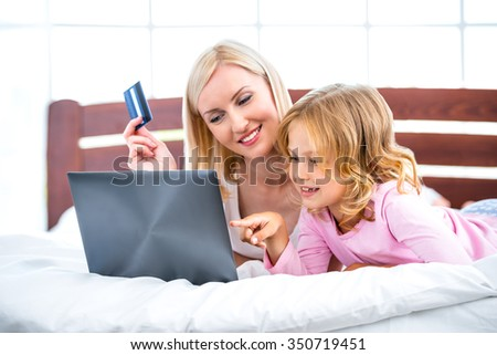 Photo of young woman and her daughter lying on nice white bed. Girls making shopping online