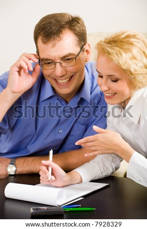 Photo of young woman and smiling man discussing a working project at meeting