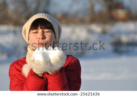Photo of young woman blowing snow from her hands - stock photo