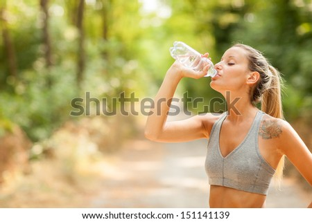 Photo of young woman drinking water after running session - stock photo