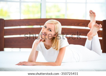 Photo of young woman lying on nice white bed. Young woman demonstrating quality of mattress - stock photo