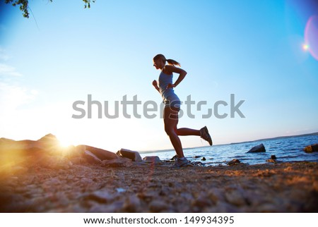 Photo of young woman running on the beach at sunrise - stock photo