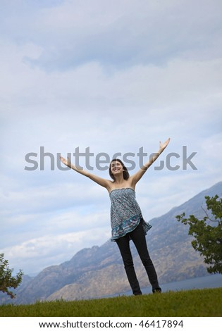 Photo of young woman standing in nature setting with arms raised toward sky. - stock photo