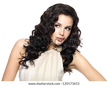 Photo of  young  woman with beauty long curly hair. Fashion model looking away - stock photo