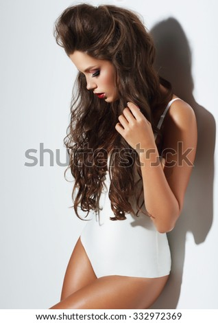 Photo of young woman with beauty long curly hair. Fashion model posing at studio. - stock photo