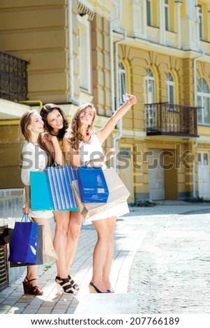 Photo on the phone. Three attractive young girl holding shopping bags while doing selfie on a cell phone outdoors. Girls laughing and smiling at the camera - stock photo