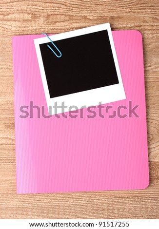 Photo paper and pink notebook on wooden background - stock photo