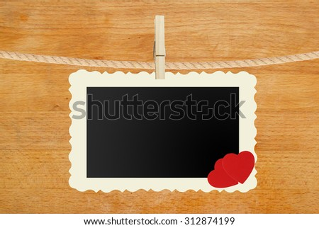 photo paper hanging with two red hearts on rope on wooden background - stock photo