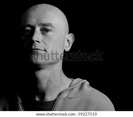 photo portrait male shaved head close up black isolated. male head face in shade.