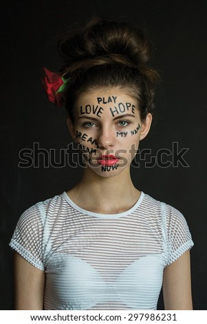 photo portrait of a girl with a rose in her hair with the words written on her face
