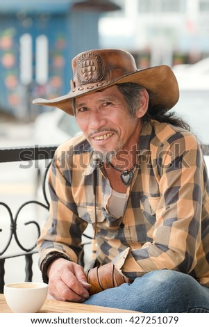 Photo-portrait of a man in a hat drinking coffee...