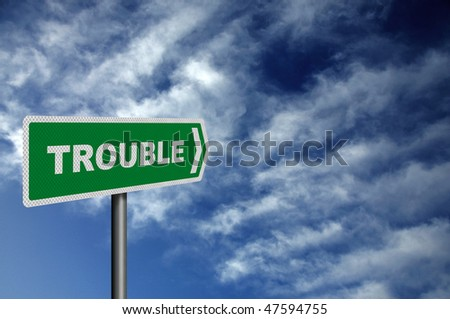 Photo realistic metallic reflective 'Trouble Ahead' road sign, against a dark, stormy sky. With space for your text overlay / editorial
