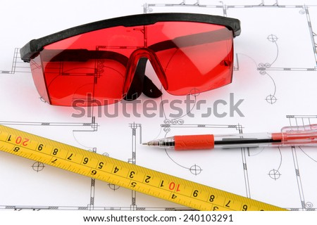 photo red protective spectacles and red pen and measuring tape on plans - stock photo
