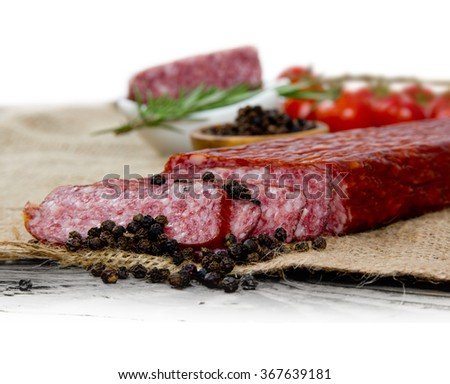 Photo salami with herbs and spice on wooden board
