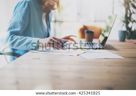 Photo Sales Manager Working Modern Office.Woman Use Generic Design Laptop and Holding Pencil.Account Department Work New Startup project.Process at Wood Table.Horizontal.Burred Background.Film effect