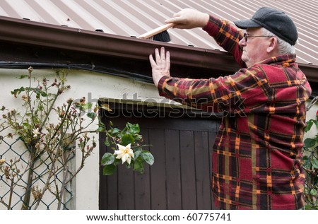photo senior male cleaning out gutter outside house