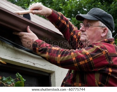 photo senior male cleaning out gutter outside house - stock photo
