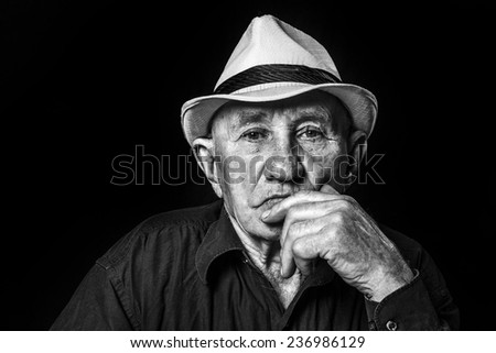 photo senior male retired wearing a hat on black - stock photo