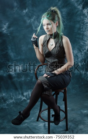 Photo session of the pretty young blonde girl with green hair in the steampunk style - stock photo