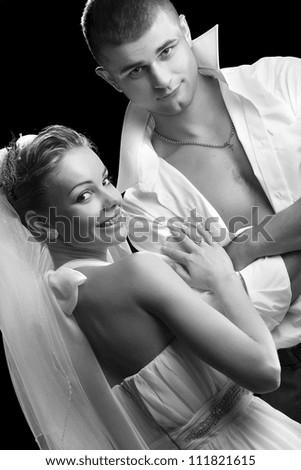 photo shoot of two Beautiful newlyweds on a black backgroun - stock photo