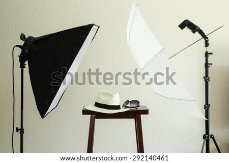 Photo shoot props for a social media profile picture: hat and sunglasses. Includes a softbox, speedlight/strobe, white umbrella. Neutral textured wall background. - stock photo