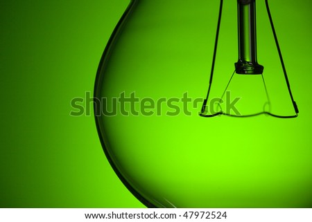 photo shot of detail of light bulb on green background - stock photo