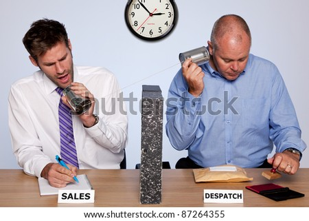 Photo showing the behind the scenes reality of the sales and despatch departments for a small business, both guys sharing the same desk and communicating via a tin can phone. - stock photo
